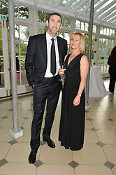 Footballer MARTIN KEOWN and his wife NICOLA at 'A Night of Champions' an evening to raise funds for the Mo Farah Foundation held at The Hurlingham Club, London on 28th August 2014.