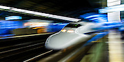 Shinkansen, at speed, passing through a station. Japan.