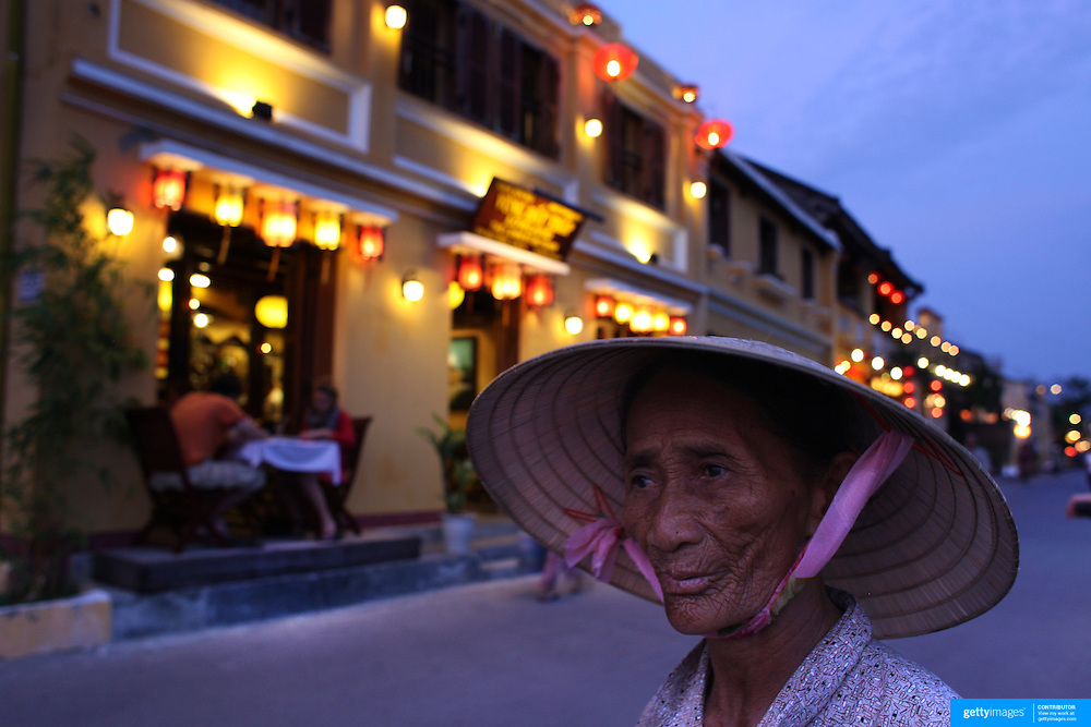 An elderly Vietnamese lady in street scene in Hoi An, Vietnam. Hoi An is an ancient town and an exceptionally well-preserved example of a South-East Asian trading port dating from the 15th century. Hoi An is now a major tourist attraction because of its history. Hoi An, Vietnam. 5th March 2012. Photo Tim Clayton