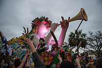 The Mardi Gras crowd watching the Krewe Of Endymion parade on Canal Street raise their hands as a float passes in hopes of catching beads or other objects thrown by the costumed men on the float. New Orleans, Louisiana