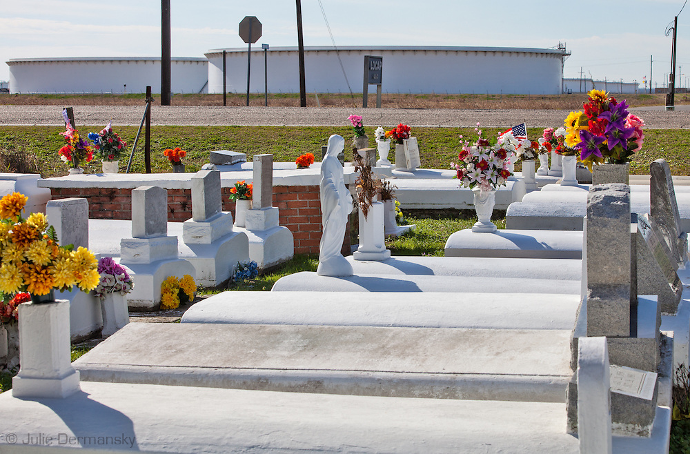 "Graveyard across the street from oil tanks at the St. James Strategic Petroleum Reserve Terminal  connected to Bayou Choctaw, one of four sites on the Gulf of Mexico, each located near a major center of petrochemical refining and processing, in this case Baton Rouge. Strategic Petroleum Reserve (SPR) is an emergency fuel store of oil maintained by the United States Department of Energy and is  located  across from  the Mississippi River in the stretch between Baton Rouge and New Orleans,  is part of a large concentration of chemical and oil companies that was formerly referred to as the ""Petrochemical Corridor,"" but now is know as ""Cancer Alley.""  Many cases of cancer have occurred  in communities on both sides of the river though the Louisiana Tumor Registry claims the numbers are not higher then the national average."