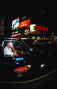 A cab driver passes through Piccadilly Circus, London, U.K, 1990s.