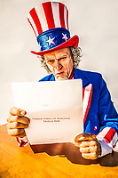 Uncle Sam character looking at a paper report on the USA deficit bill.