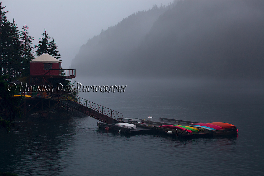 A bright line of kayaks are stowed on the dock awaiting a brake in the rain. Orca Island Cabins, Humpy Cove, Alaska