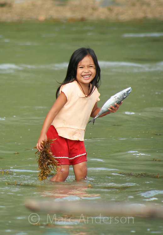 A little girl standing in the sea holding a fish and seaweed, El Nido, Palawan, Philippines.