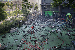 © Licensed to London News Pictures. 14/06/2017. London, UK. A childrens play area is filled with debris directly under Grenfell Tower on the Lancaster West Estate -  scene of a huge fire in west London. The blaze engulfed the 27-storey building with 200 firefighters attending the scene. A number of fatalities have been reported. Photo credit: Peter Macdiarmid/LNP