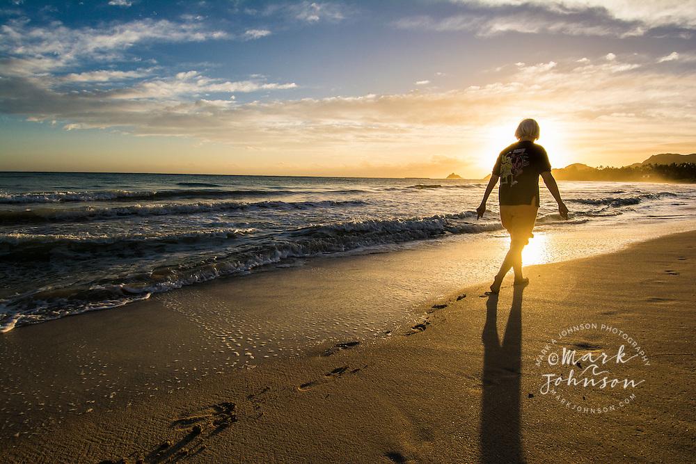 Woman walking on the beach at sunrise, Kailua, Oahu, Hawaii