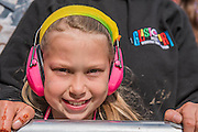 A child in ear defenders in teh front row with the fans awaiting Madness at the Pyramid Stage - The 2016 Glastonbury Festival, Worthy Farm, Glastonbury.
