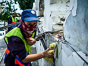 23 AUGUST 2017 - BANGKOK, THAILAND: A Bangkok city worker scrubs the walls of Pom Mahakan. Bangkok city officials this week started cleaning up the area around cremation site for Bhumibol Adulyadej, the Late King of Thailand. Work started by cleaning Pom Mahakan, a historic fort about two kilometers northeast of the cremation site. They are going to scrub and paint the fort's historic exterior walls, which were built in the late 18th century. The King, who died on 13 October 2016, will be cremated on 26 October 2017.      PHOTO BY JACK KURTZ