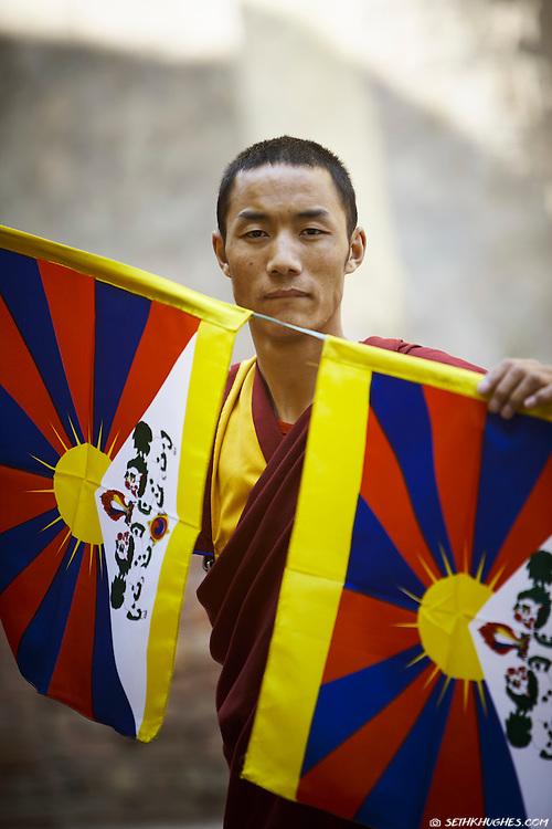 A Tibetan Buddhist monk prepares to hang Tibetan flags in McLeodGanj, Dharamsala, India.