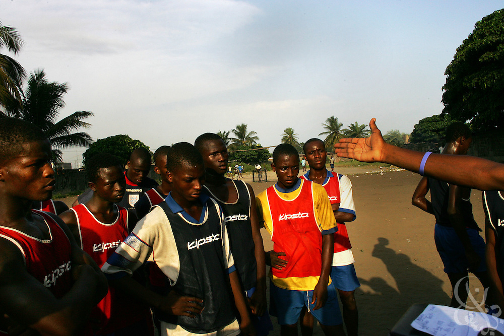 "The"" Almighties of Koomassi"" academy football club listens to coaches during a practice in the Koomassi neighborhood of Abidjan, Côte d'Ivoire February 17, 2006.  Trying to mimic the successes of ASEC academy, more than 300 rival football academies have been started in Abidjan. Parents hoping of their children will become national team members or pro european league players often become indebted in order to put their children into the copycat academies, which focus on football skills, but do little to educate the young Ivorians who attend them."