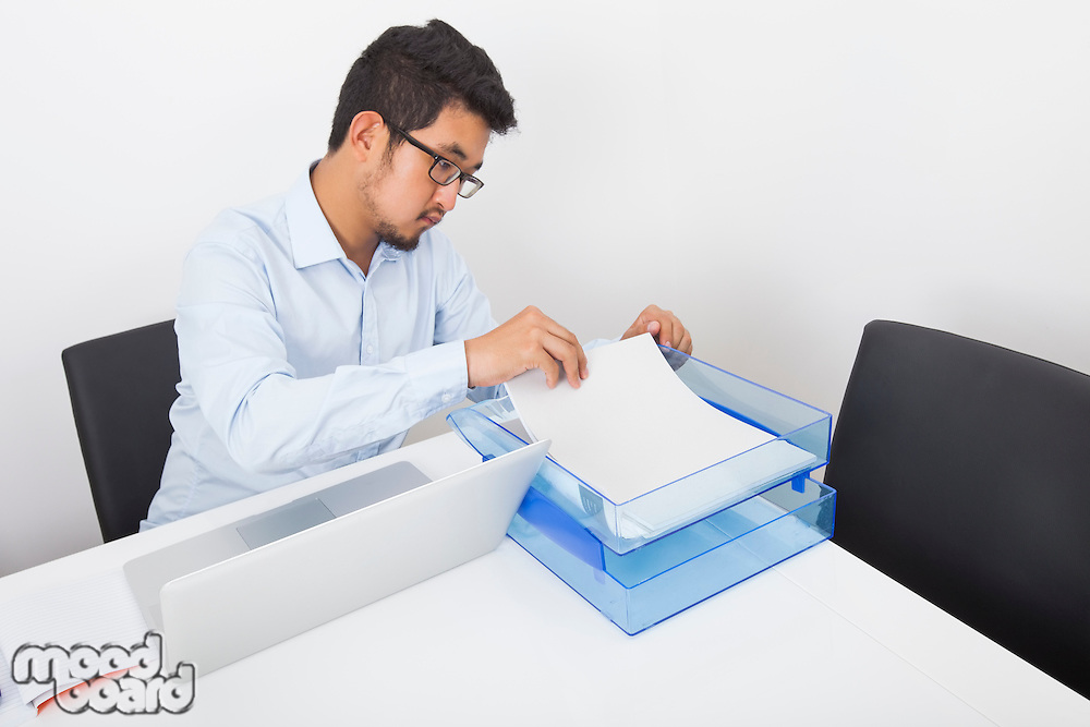 Businessman searching documents at desk in office
