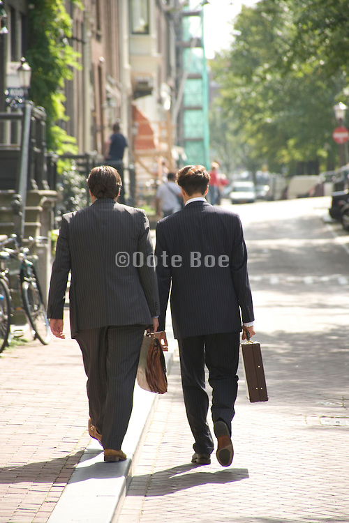 two business men walking through the streets of Amsterdam