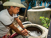 14 JULY 2015 - THAILAND: Provincial water department workers deliver water to a private residence in Nakhon Nayok province. The drought that has crippled agriculture in central Thailand is now impacting residential areas near Bangkok. The Thai government is reporting that more than 250,000 homes in the provinces surrounding Bangkok have had their domestic water cut because the canals that supply water to local treatment plants were too low to feed the plants. Local government agencies and the Thai army are trucking water to impacted communities and homes. Roads in the area have started collapsing because of subsidence caused by the retreating waters. Central Thailand is contending with drought. By one estimate, about 80 percent of Thailand's agricultural land is in drought like conditions and farmers have been told to stop planting new acreage of rice, the area's principal cash crop.       PHOTO BY JACK KURTZ
