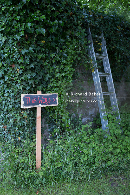A hand-painted sign showing guests where to go before a 50th birthday party in the Herefordshire countryside, on 23rd June 2019, in Kington, Herefordshire, England.