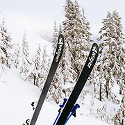 A pair of Wagner Customs Skis sit in the snow at sunset in the backcountry near Mount Baker Ski Area.