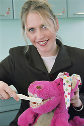 Oral Health promoter demonstrating tooth brushing technique on a puppet,