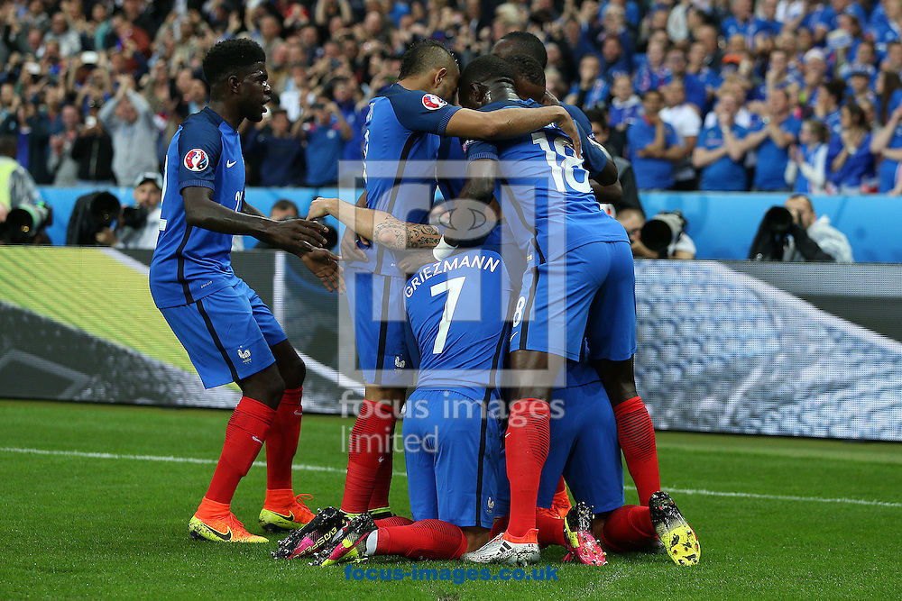 The French players mob Olivier Giroud of France after he scored his side's 1st goal during the quarter final match at Stade de France, Paris<br /> Picture by Paul Chesterton/Focus Images Ltd +44 7904 640267<br /> 03/07/2016