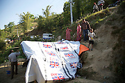 A Nepalese family start to fix a UK aid tarpaulin to the roof of their temporary shelter in Sindhupalchowk district, about 40 miles from Kathmandu. Their home, which used to stand nearby, was almost completely destroyed by the earthquake which struck the country on 25 April 2015. <br /> <br /> &quot;I don't know how we are going to rebuild&quot;, says Parvita.<br /> <br /> &quot;But these plastic sheets will at least help to keep us dry when the monsoon comes, and they'll help us keep our animals and wheat dry too.&quot;<br /> <br /> UK aid shelter kits are being distributed to thousands of people who have lost their homes in remote parts of Nepal. Working with NGOs including MedAir, ACTED and Shelterbox, the kits are being distributed by helicopter, road and ultimately, heads, as they are carried up steep mountain trails to where they are needed.<br /> <br /> Pictures: Russell Watkins/DFID