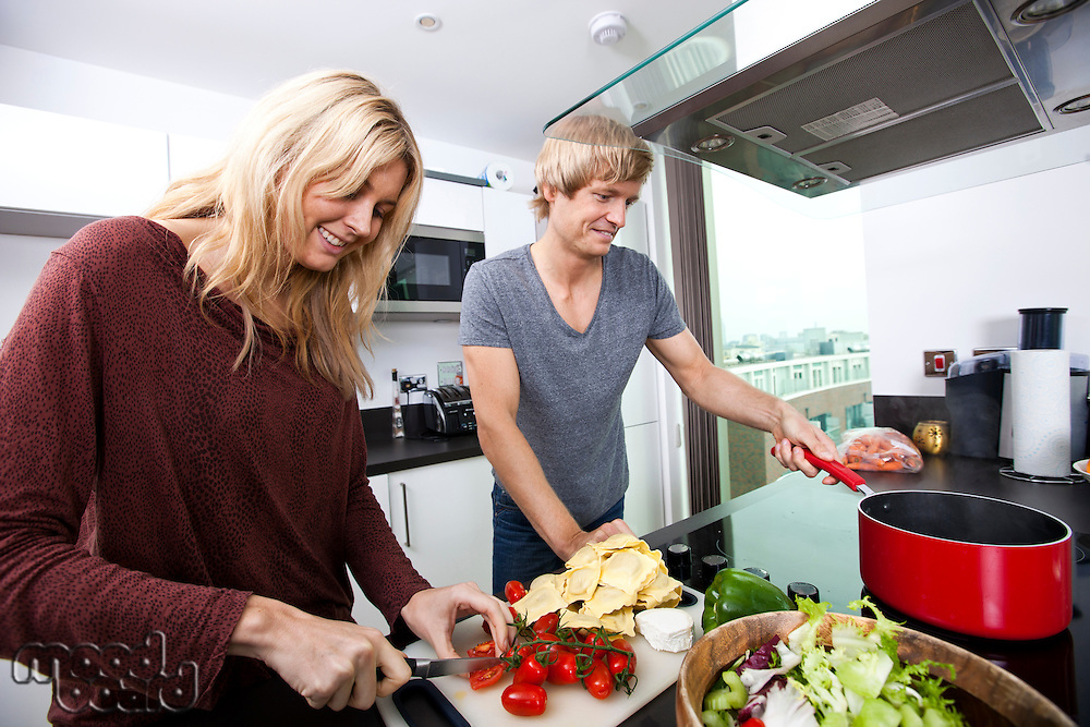 Smiling Caucasian couple cooking together in kitchen