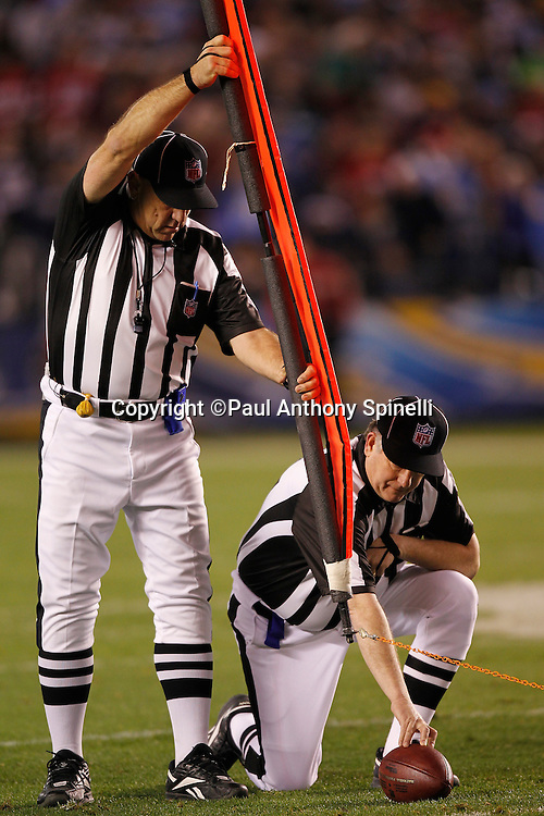 NFL referees measure for a first down during the San Diego Chargers NFL week 15 football game against the San Francisco 49ers on Thursday, December 16, 2010 in San Diego, California. The Chargers won the game 34-7. (©Paul Anthony Spinelli)