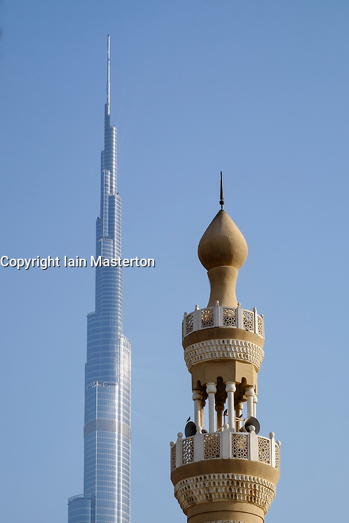 Burj Khalifa tower and contrasting  mosque minaret  in  Dubai United Arab Emirates