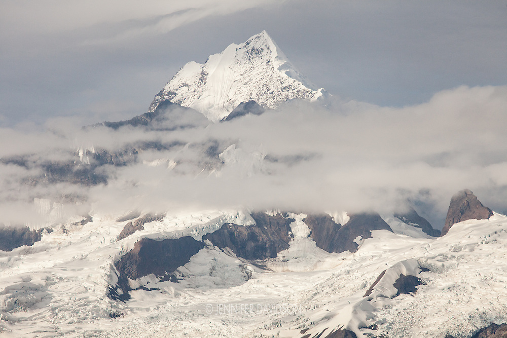 Mount Wilbur ascends above the clouds near Johns Hopkins Glacier in Glacier Bay National Park, Alaska.
