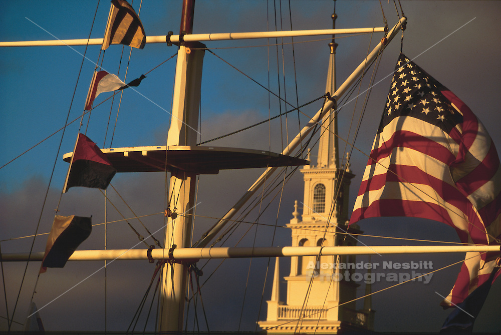 USA, Newport, RI - Nautical/maritime signal flags with the American flag flying from the Bowen's wharf flag mast frame Newport's Trinity Church..
