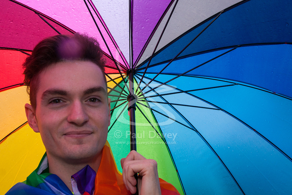 London, June 28th 2014. A young man shelters from the rain as Gay Pride revellers assemble on Baker Street ahead of the parade.