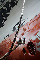 Two men in cherry picker working at ship in dry dock low angle view