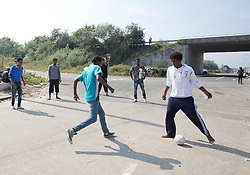 © Licensed to London News Pictures. 30/08/2015. Calais, France. Youngsters play football at the entrance of the refugee camp in Calais, also known as the Jungle. Tomorrow the French PM, Manuel Valls, will visit the day centre Jules Ferry at the camp. Photo credit : Isabel Infantes/LNP