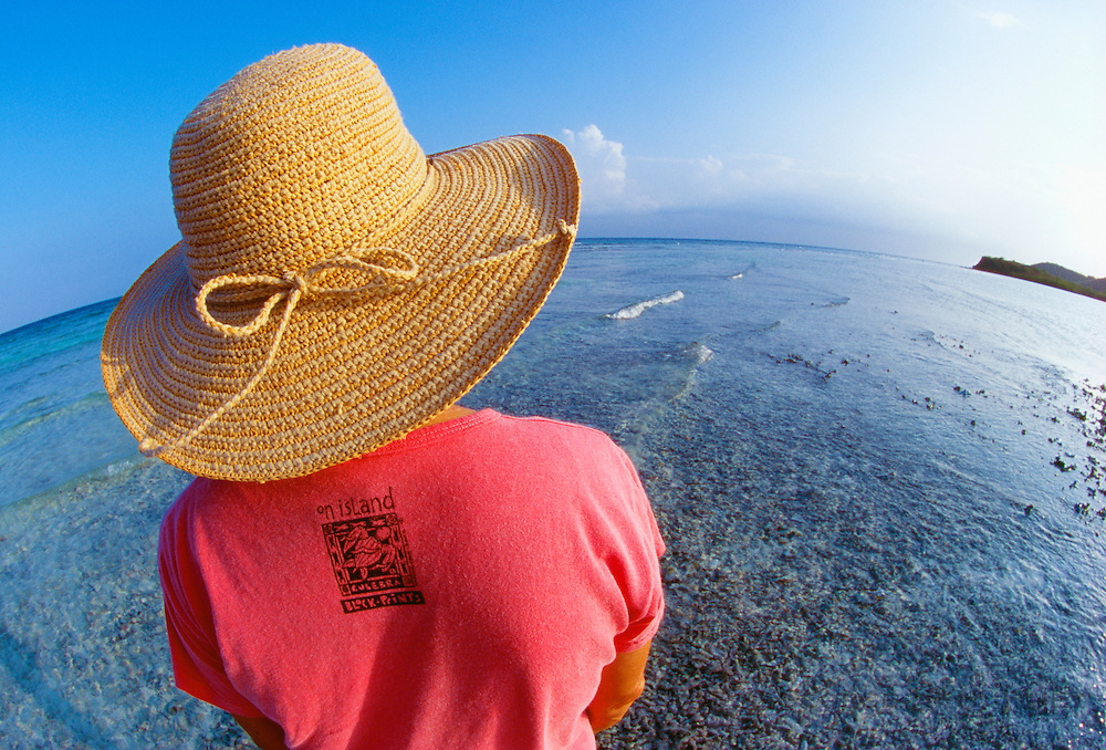356205-1013B ~ Copyright:  George H. H. Huey ~ Woman with hat and Culebra, Puerto Rico T-shirt on a beach on the Island of Culebra, off the east coast of Puerto Rico. Caribbean.  Release #132