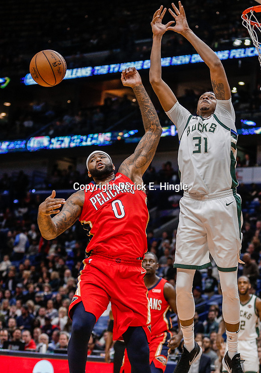 Dec 13, 2017; New Orleans, LA, USA; New Orleans Pelicans center DeMarcus Cousins (0) knocks away the ball from Milwaukee Bucks forward John Henson (31) during the first quarter at the Smoothie King Center. Mandatory Credit: Derick E. Hingle-USA TODAY Sports