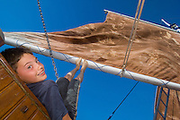 An eight-year old boy tries his hand (and feet) at trimming the sails on a chartered liveaboard  boat modeled after a traditional Indonesian ketch in Komodo National Park, Indonesia. Experiential travel photography by Djuna Ivereigh.