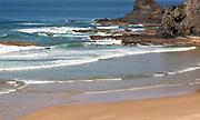 Atlantic Ocean waves breaking on rocky coastline of the headland and sandy bay beach, Praia de Odeceixe, Algarve, Portugal, Southern Europe