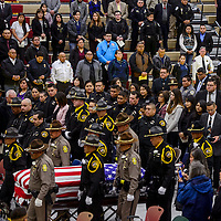 McKinley County Sheriffs officers and Navajo Nation Police officers escort the casket of McKinley County Sheriffs officer Christopher Tsosie through a crown during a memorial service Wednesday at Rehoboth High School in Gallup.
