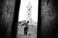 ©ANGOLA 2002. Children playing infront of a bullet pierced church in Kuito..Picture featured in book KIDS photos by Markus Marcetic, published 2007.