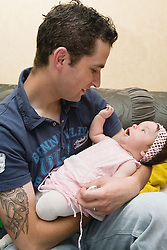 Polish father holding baby daughter in his arms,