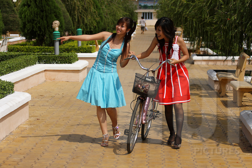 Two young trendy vietnamese girls walks in park of Can Tho, Vietnam, Southeast Asia