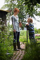 Mother and son (5-6) with spade in countryside