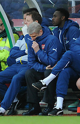 Arsenal Manager, Arsene Wenger hides his head in his coat as his side lose at half time by 3 - 0 - Photo mandatory by-line: Dougie Allward/JMP - Mobile: 07966 386802 - 06/12/2014 - SPORT - Football - Stoke - Britannia Stadium - Stoke City v Arsenal - Barclays Premie League