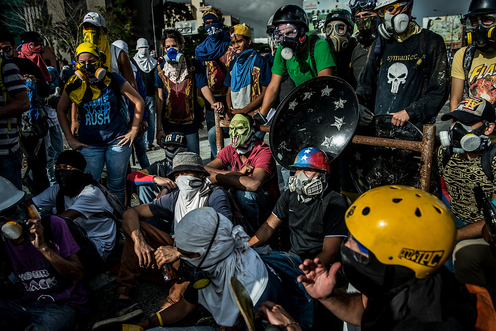 CARACAS, VENEZUELA - MAY 26, 2017:  Anti-government protesters hold a meeting to discuss strategy during a lull in fighting after taking back control of the main highway that runs through Caracas from government security forces. The streets of Caracas and other cities across Venezuela have been filled with tens of thousands of demonstrators for nearly 100 days of massive protests, held since April 1st. Protesters are enraged at the government for becoming an increasingly repressive, authoritarian regime that has delayed elections, used armed government loyalist to threaten dissidents, called for the Constitution to be re-written to favor them, jailed and tortured protesters and members of the political opposition, and whose corruption and failed economic policy has caused the current economic crisis that has led to widespread food and medicine shortages across the country.  Independent local media report nearly 100 people have been killed during protests and protest-related riots and looting.  The government currently only officially reports 75 deaths.  Over 2,000 people have been injured, and over 3,000 protesters have been detained by authorities.  PHOTO: Meridith Kohut