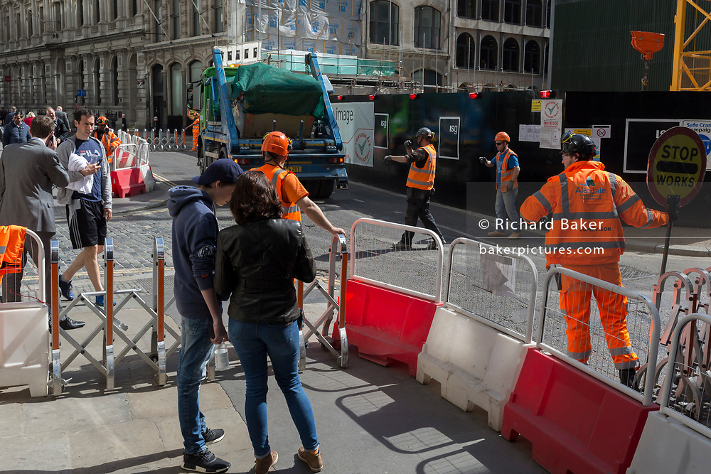 Construction workers temporarily close Lombard Street to pedestrians as a skip lorry exits their site, in the heart of the capital's financial district, on 19th April, in the City of London, England.