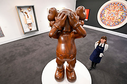 © Licensed to London News Pictures. 07/02/2020. LONDON, UK. A technician views ''At This Time '' by Kaws, (Est. £700,000 - 900,000). Preview of Sotheby's Contemporary Art Sale in their New Bond Street galleries.  Works by artists including Francis Bacon, Yves Klein, Jean-Michel Basquiat and David Hockney will be offered for auction on 11 February 2020.  Photo credit: Stephen Chung/LNP