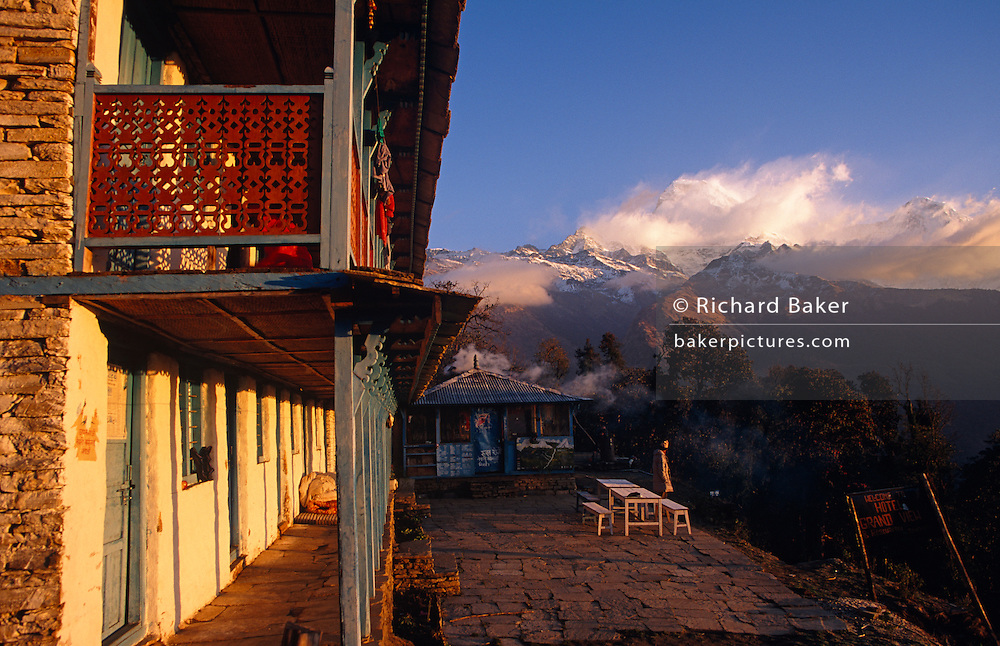 High in the Himalayan foothills, dawn arrives on a bitterly cold morning. A traveller has emerged from his rudimentary room on the left of this lodge in Nepal to stand outside staring at the spectacular landscape of snow-capped peaks in the distance. The wind is whipping snow and ice from the peaks of the Annapurna range and trekkers come from all over the world to sample the inner-peace to be discovered here in one of the most dramatic locations on the planet. Villages such as these partly-depend on the agriculture of rice-growing and also on the passing tourist trade. Western trekkers walk through these tiny communities on their way up the series of climbing trails of the Annapurna Conservation Sanctuary circuit, a sometimes rigorous walk from the low hills of Pokhara to the higher altitudes of Annapurna, the (26,000 feet (8,000 metre) peak.