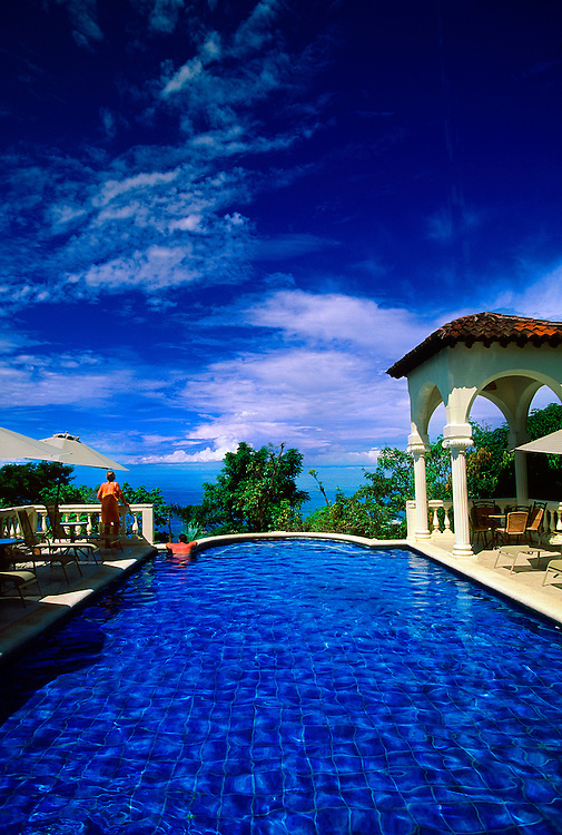 Couple enjoying swimming pool at the Hotel Parador Boutique Resort & Spa overlooking the Pacific Ocean, Manuel Antonio, Costa Rica