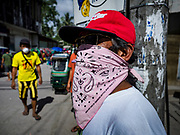 23 JANUARY 2018 - CAMALIG, ALBAY, PHILIPPINES: People in Camalig cover their faces with masks because of an ash fall from the Mayon volcano. The Mayon volcano continued to erupt Tuesday, although it was not as active as it was Monday. There were ash falls in communities near the volcano. This is the most active the volcano has been since 2009. Schools in the vicinity of the volcano have been closed and people living in areas affected by ash falls are encouraged to stay indoors, wear a mask and not participate in strenuous activities.    PHOTO BY JACK KURTZ