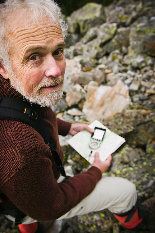 A portrait of a man using a map and compass.