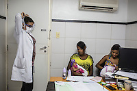 RECIFE, BRAZIL - JANUARY 8: Pediatrics doctor Danielle Cruz at The Professor Fernando Figueira Institute of Medicine, a public hospital, puts her mask on before doing a follow-up visit of three-month-old Isabella Vitoria da Silva Honoro who was born with a suspected zika-related microcephaly. Aline Maria da Silva Souza, 16, holds her nice, and mother, Fernanda da Silva Souza, 18, gathers her paperwork.<br /> <br /> The mosquito-borne Zika virus continues to spread in Brazil, alarming health officials and expecting mothers that their babies will be born with abnormal brain development called microcephaly. While researchers have yet to make a connection, Brazil has the highest number of babies born with mircocephaly - the most cases in Recife, Pernambuco - from mothers who tested positive to the Zika virus.  There are about 3,530 suspected cases of zika-related microcephaly in Brazil.