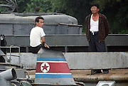 North Koreans in the town of Sunuiju on the Yalu River July 9, 2006. North Korea promised to use force against any country that tries to pressure it into a halt of its missile launches. DPRK, north korea, china, dandong, border, liaoning, democratic, people's, rebiblic, of, korea, nuclear, test, rice, japan, arms, race, weapons, stalinist, communist, kin jong il